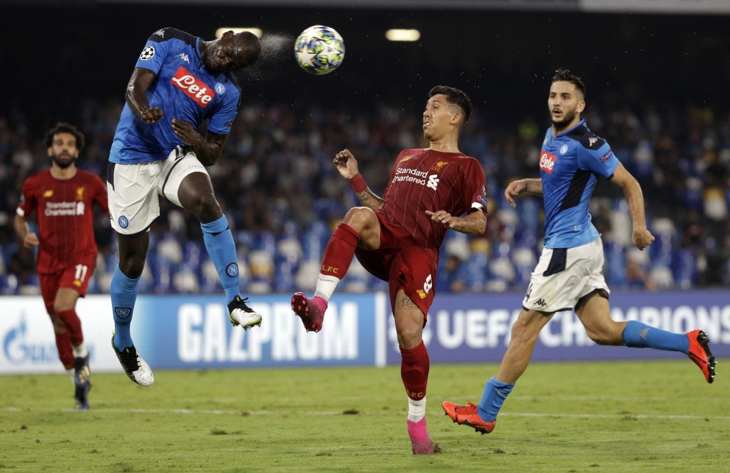 Napoli's Kalidou Koulibaly, left, heads the ball as Liverpool's Roberto Firmino tries to stop him during the Champions League Group E soccer match bet...