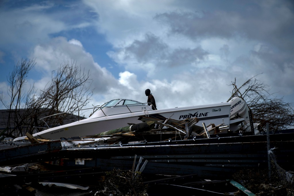 A soldier behind a boat sitting in the rubble of Hurricane Dorian in Abaco, Bahamas, Monday, Sept. 16, 2019. Dorian hit the northern Bahamas on Sept. ...