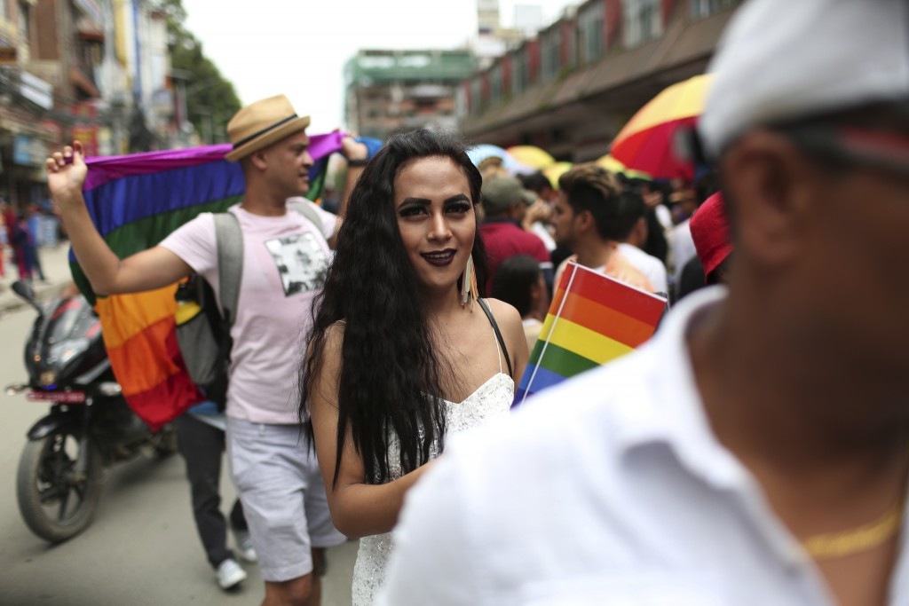 In this Aug. 16, 2019, photo, a participant holds a rainbow flag and marches in a gay pride parade in Kathmandu, Nepal. Nepal seized the lead in equal