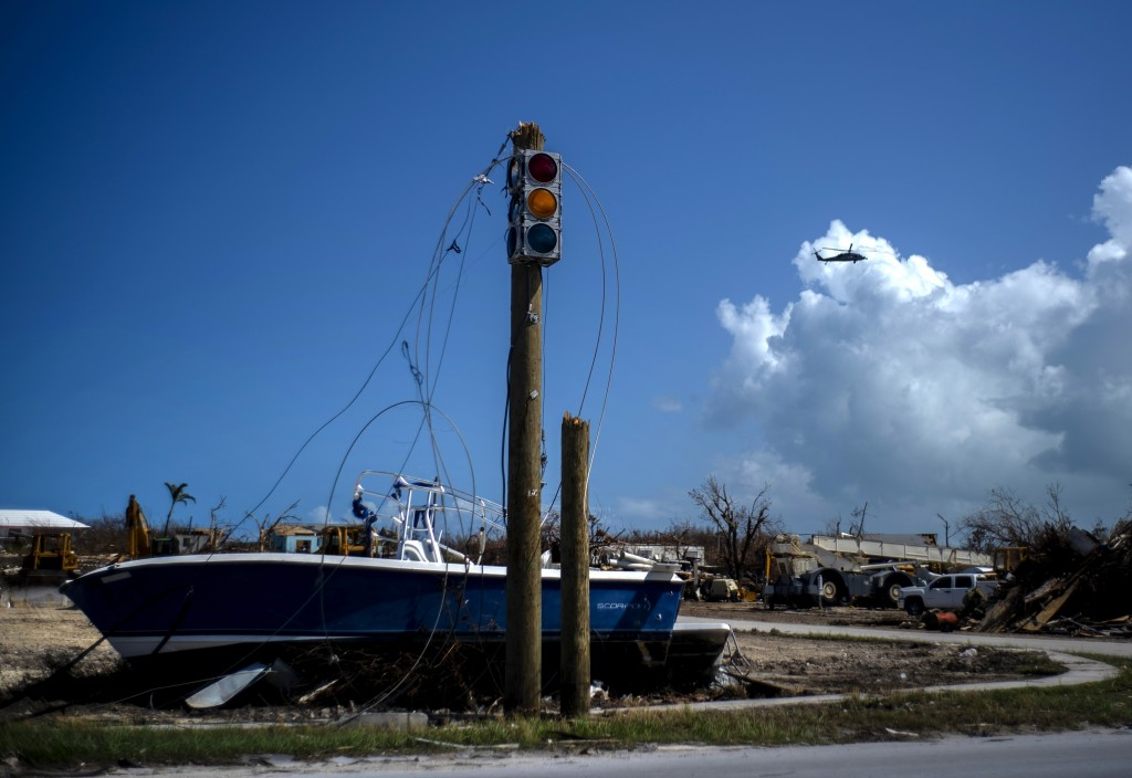 A boat sits on dry land next to a traffic light in the aftermath of Hurricane Dorian, in Abaco, Bahamas, Tuesday Sept. 17, 2019. Dorian hit the northe...