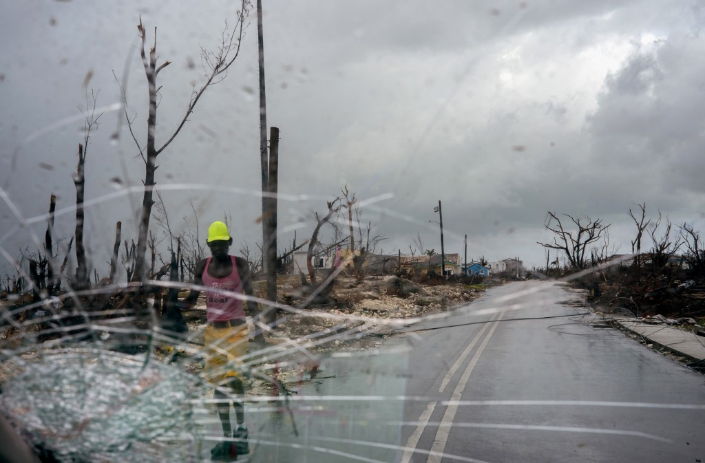 Trees destroyed by Hurricane Dorian line a road as a man walks by, in Abaco, Bahamas, Monday, Sept. 16, 2019. Dorian hit the northern Bahamas on Sept....