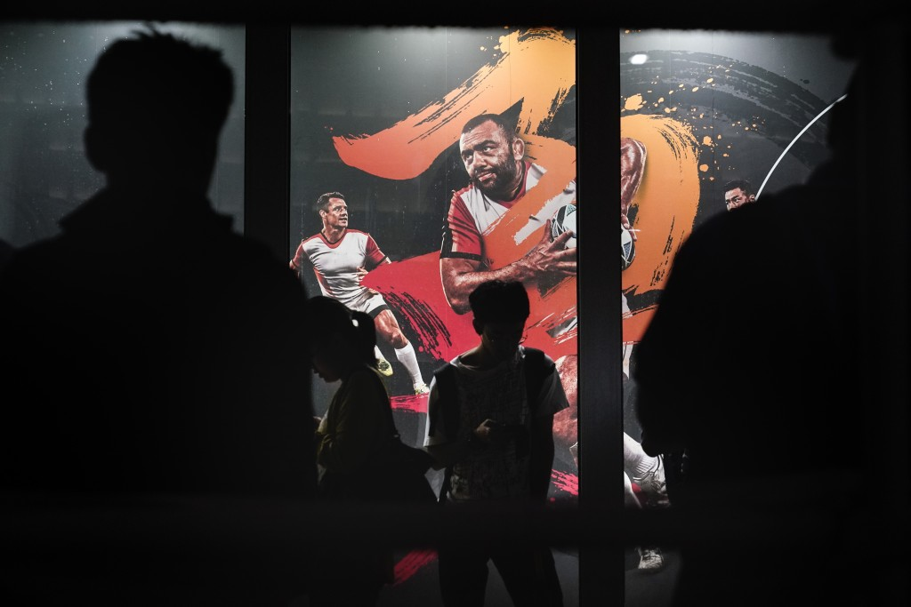 People are silhouetted against an advertisement showing an image of Japan captain Michael Leitch outside an official merchandise store of the Rugby Wo...