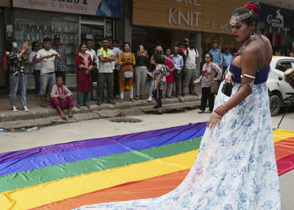In this Aug. 16, 2019, photo, a participant stands beside a rainbow flag before a gay pride parade in Kathmandu, Nepal. Nepal seized the lead in equal