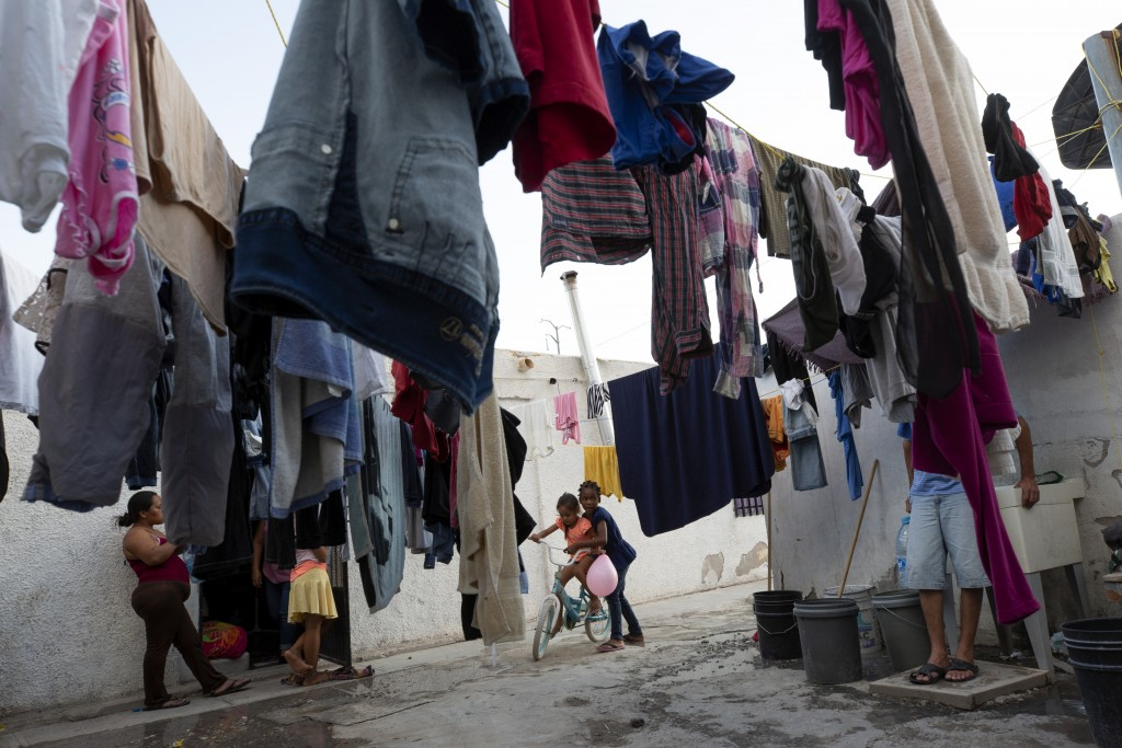 In this July 26, 2019, photo, a girl from Africa plays with a girl from Honduras at El Buen Pastor shelter for migrants in Cuidad Juarez, Mexico. (AP