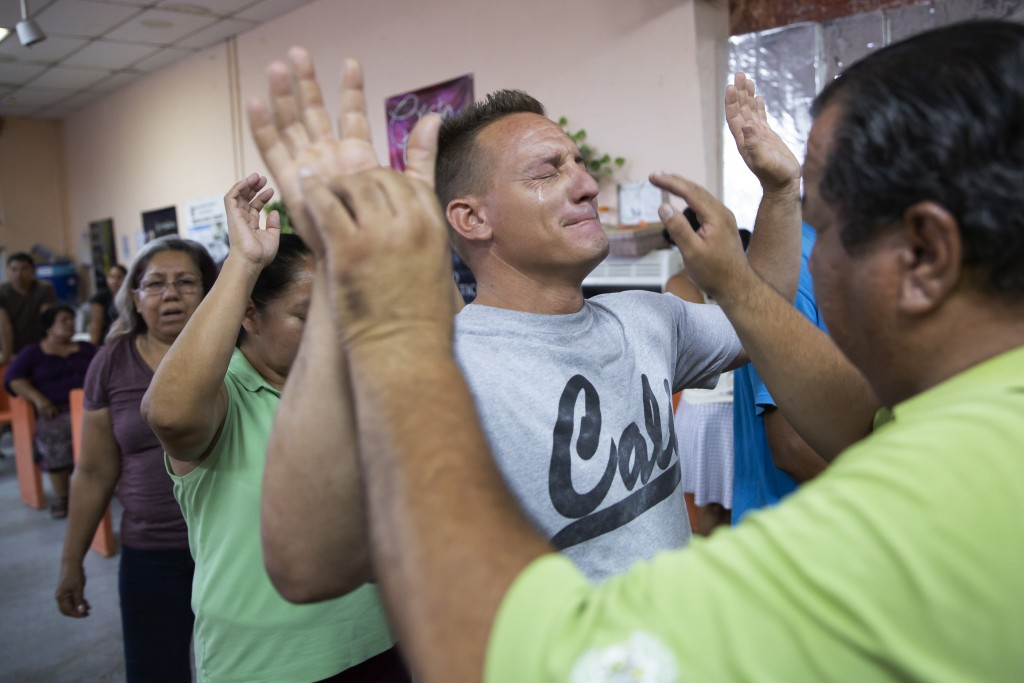 In this July 25, 2019, photo, pastor Juan Fierro, right, touches Miguel, of Cuba, during services at El Buen Pastor shelter for migrants in Cuidad Jua