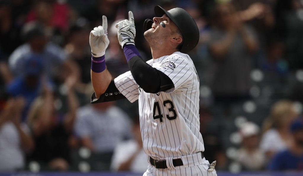 Colorado Rockies' Sam Hilliard gestures as he crosses home plate after hitting a solo home run off New York Mets starting pitcher Noah Syndergaard in ...