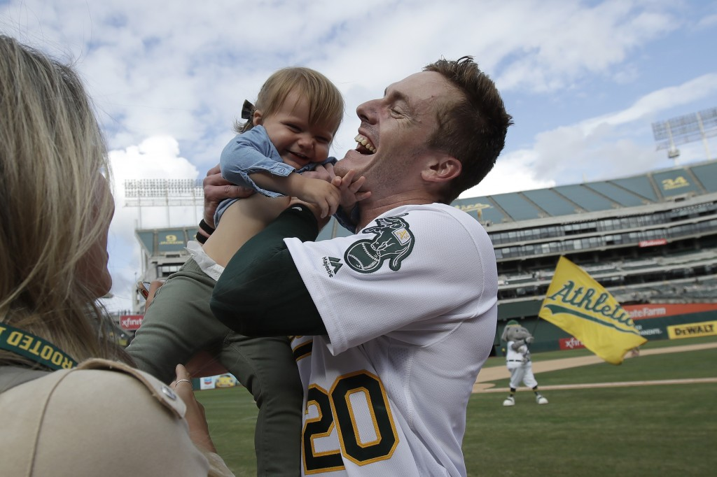 Oakland Athletics' Mark Canha (20) celebrates with his daughter Cami after the Athletics defeated the Kansas City Royals 1-0 in 11 innings a baseball