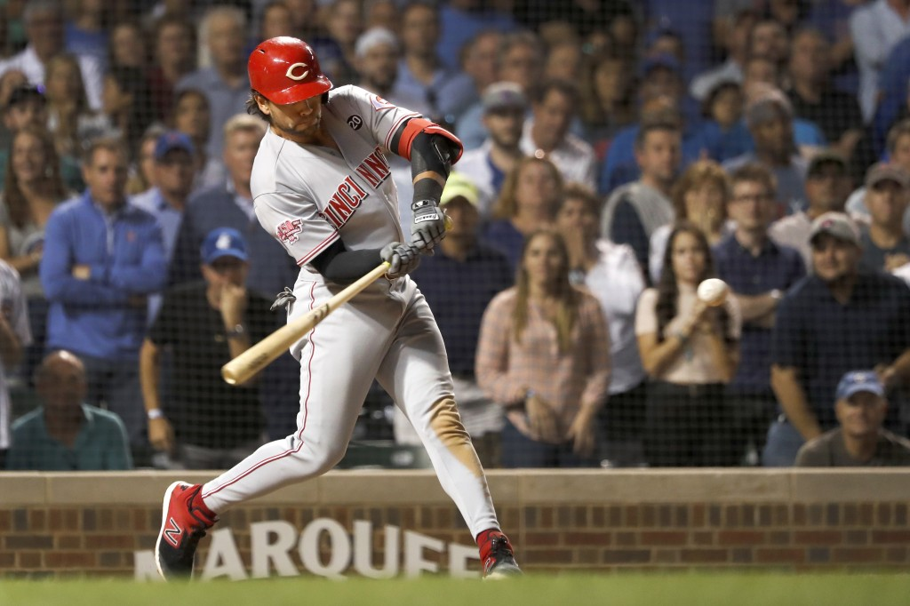 Cincinnati Reds' Alex Blandino swings for an RBI sacrifice fly off Chicago Cubs relief pitcher Kyle Ryan during the seventh inning of a baseball game