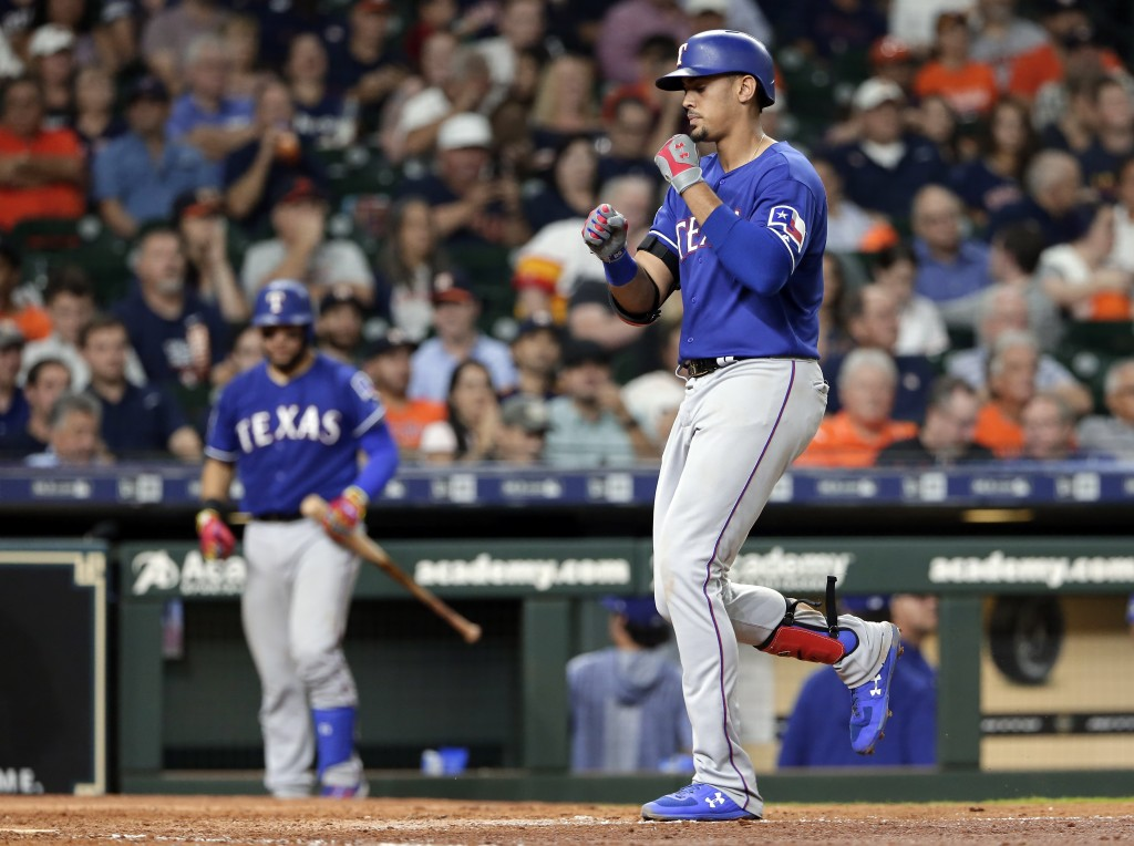 Texas Rangers' Ronald Guzman, right, reacts as he crosses the plate on his home run during the eighth inning of the team's baseball game against the H...