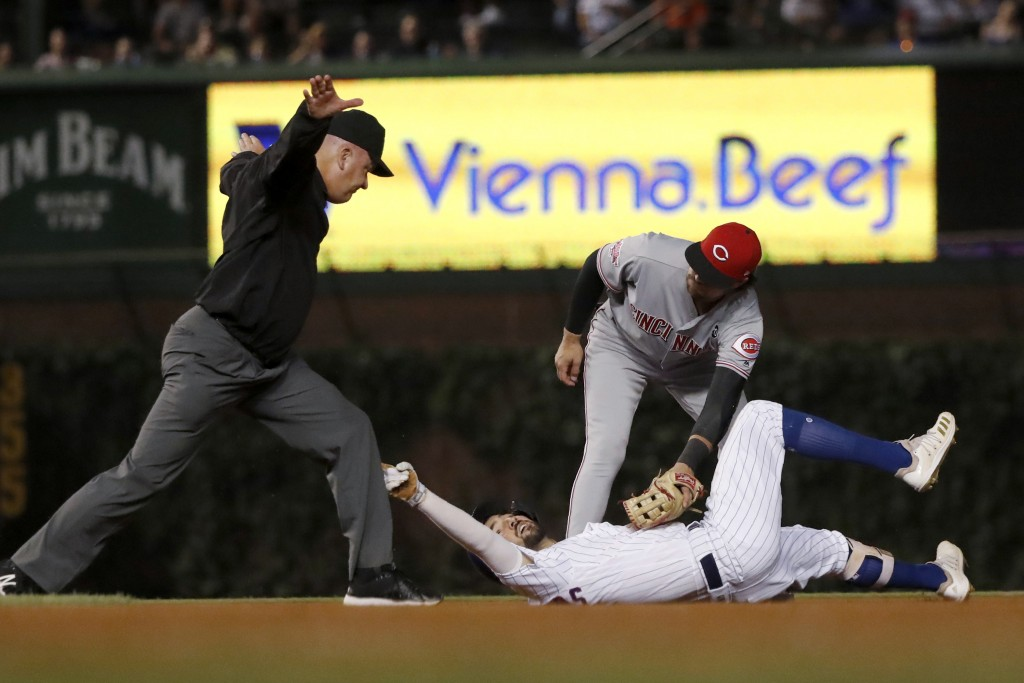 Second base umpire Jeff Nelson calls Chicago Cubs' Nicholas Castellanos safe at second as Cincinnati Reds' Alex Blandino applies a tag during the four