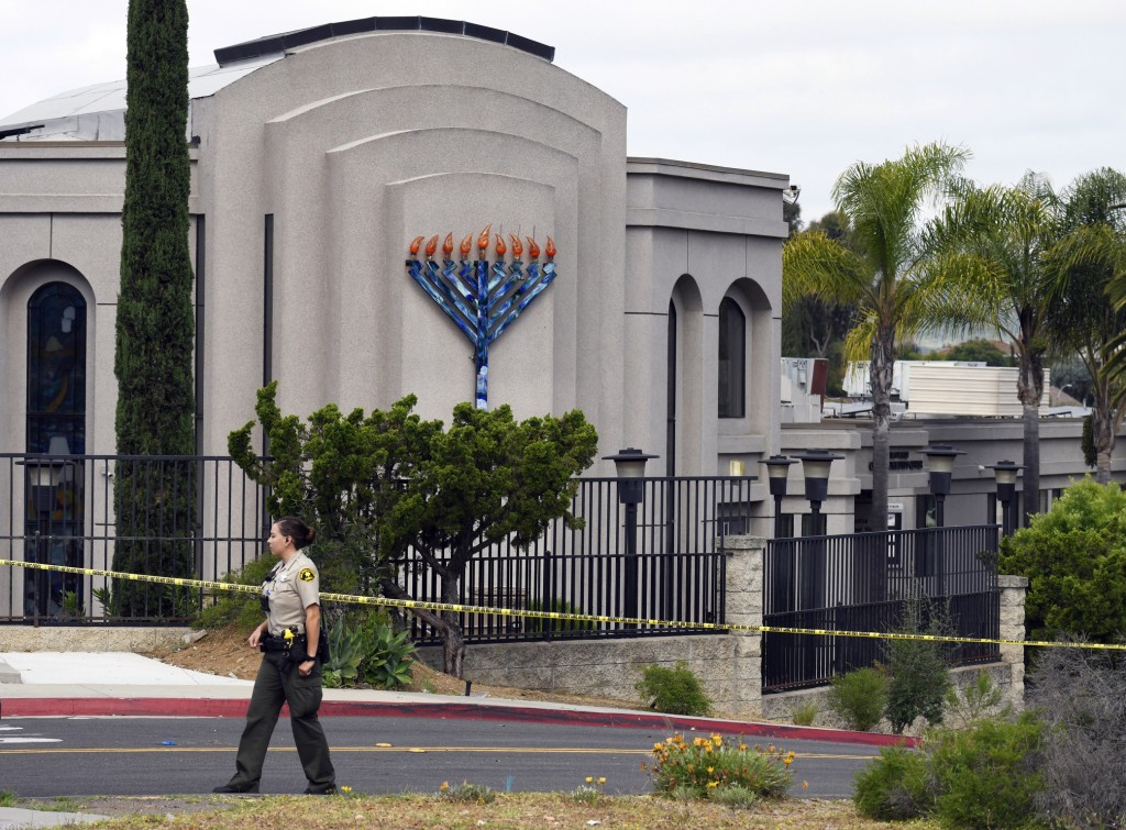 FILE - In this Sunday, April 28, 2019 file photo, a San Diego county sheriff's deputy stands in front of the Poway Chabad Synagogue in Poway, Calif. P