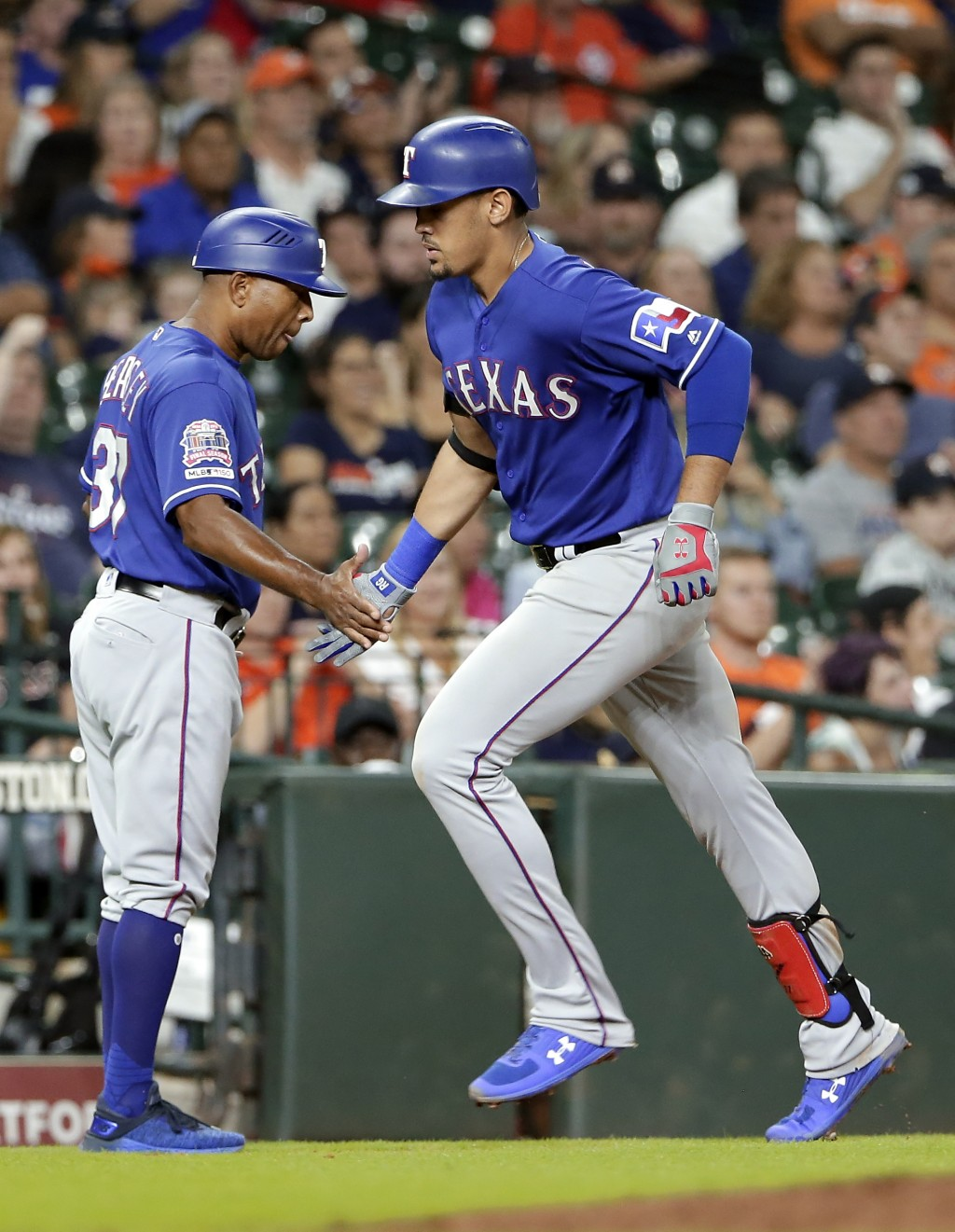 Texas Rangers third base coach Tony Beasley, left, congratulates Ronald Guzman, right, as he rounds third base on his home run during the eighth innin