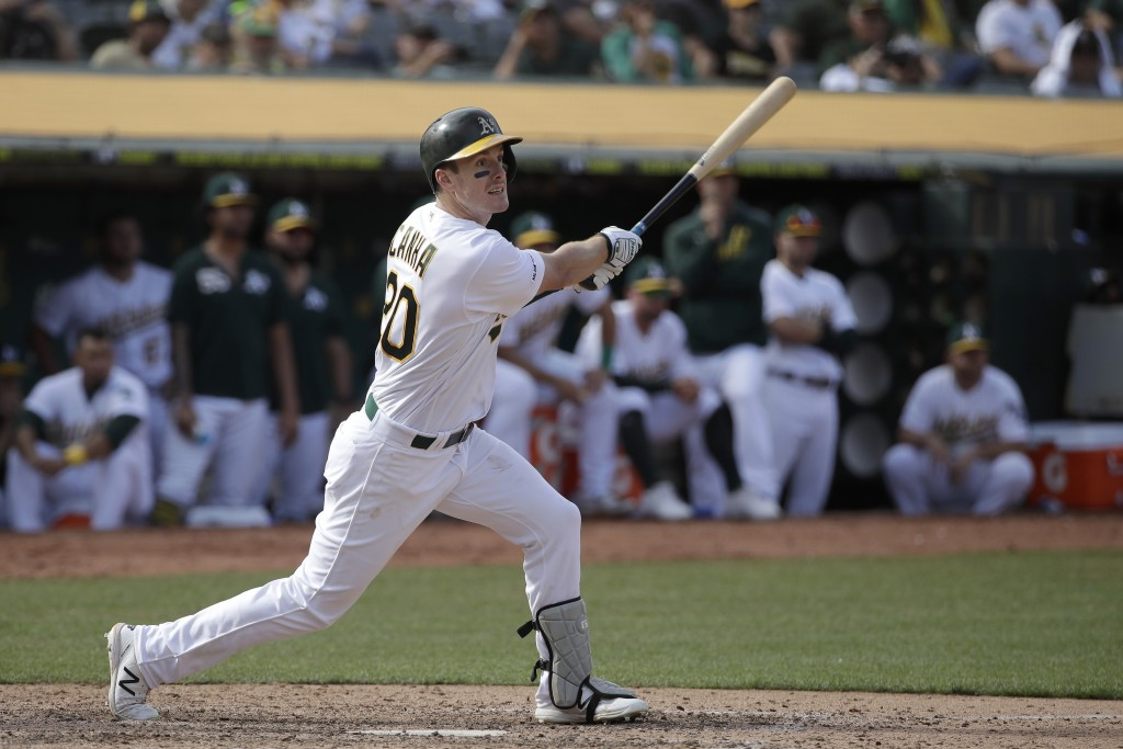 Oakland Athletics' Mark Canha hits a double to score Jurickson Profar during the 11th inning of a baseball game against the Kansas City Royals in Oakl...