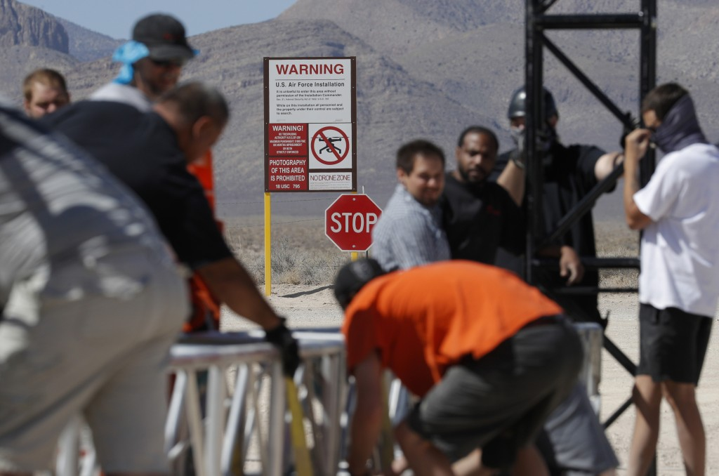 Workers erect a stage near a replica Area 51 gate sign at the Alien Research Center, Wednesday, Sept. 18, 2019, in Hiko, Nev. Visitors descending on t