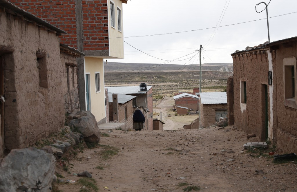 In this Sept. 13, 2019 photo, a resident walks along a dirt paved road in Orinoca, Bolivia. Orinoca, the birthplace of President Evo Morales, is a hum