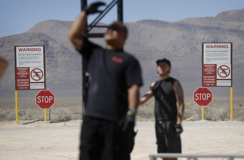 Workers erect a stage near replica Area 51 gate signs at the Alien Research Center, Wednesday, Sept. 18, 2019, in Hiko, Nev. No one knows what to expe...