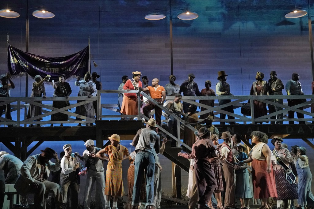 This image released by the Metropolitan Opera shows Latonia Moore as Serena, center left on stairs, and Frederick Ballentine as Sportin' Life in a sce...