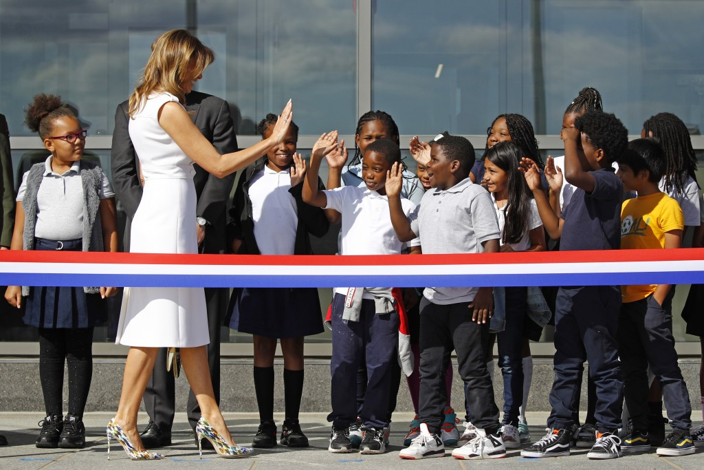 First lady Melania Trump high-fives students from Amidon-Bowen Elementary School in Washington as she arrives at a ribbon-cutting ceremony to re-open ...