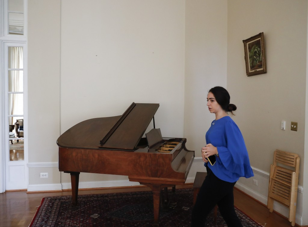 In this Sept. 17, 2019, photo, a staff member walks past a section of blank wall space above a piano where artwork once hung inside the Ambassador's r...