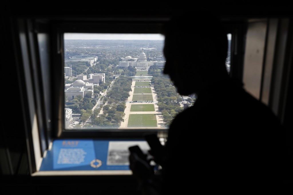A visitor looks out toward the U.S. Capitol from the Washington Monument's observation level during a press preview tour ahead of the monument's offic...