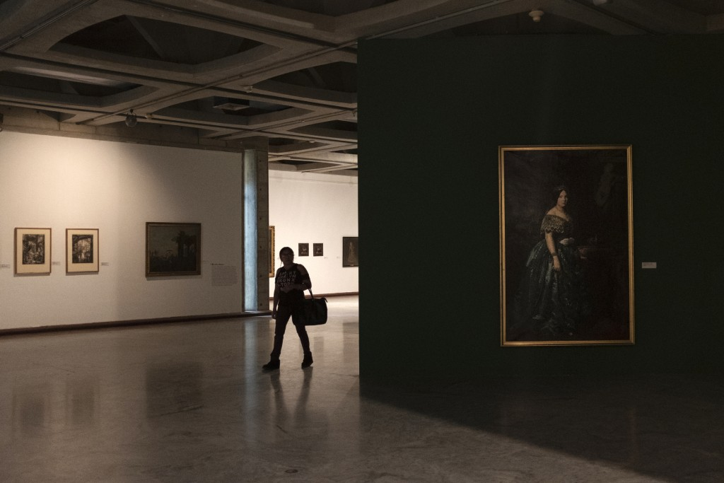 In this Sept. 17, 2019, photo, a woman walks between European paintings in the dark in the Museum of Fine Arts of Caracas, Venezuela. Only about a thi...