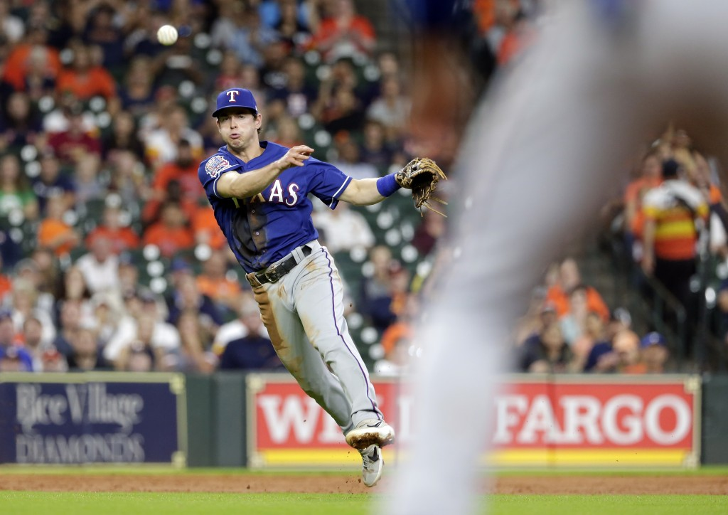 With the bases loaded and two out, Texas Rangers third baseman Nick Solak fields the hit by Houston Astros George Springer to first base for the out t...