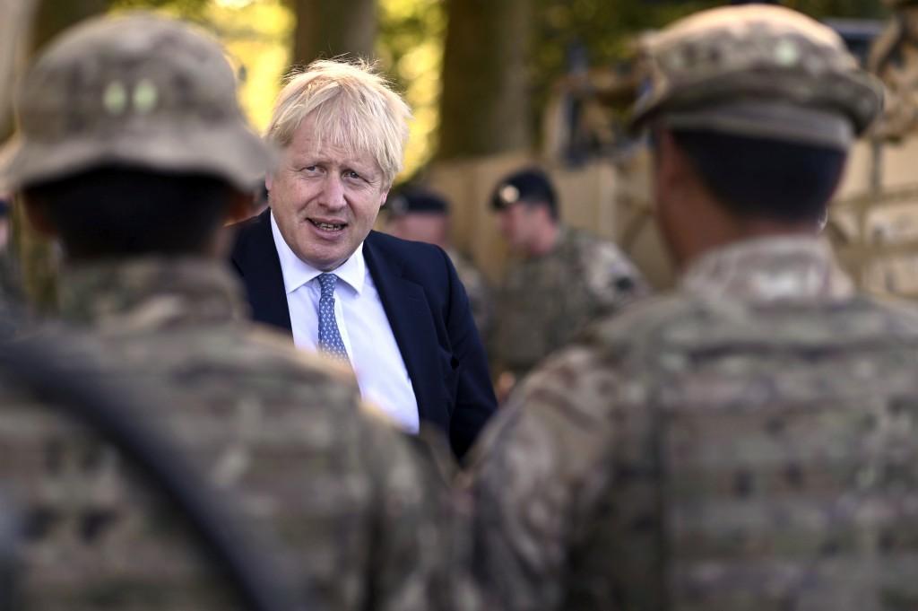 Britain's Prime Minister Boris Johnson talks to Ghurkas as he meets with military personnel on Salisbury Plain training area near Salisbury, England, ...