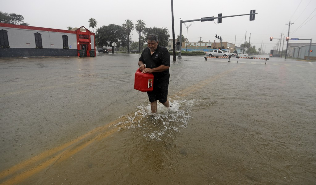 Angel Marshman carries a gas can as he walks through floodwaters from Tropical Depression Imelda to get to his flooded car, Wednesday, Sept. 18, 2019,