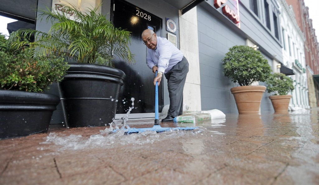Paco Vargas pushes floodwaters from Tropical Depression Imelda away from his business Wednesday, Sept. 18, 2019, in Galveston, Texas. (AP Photo/David ...