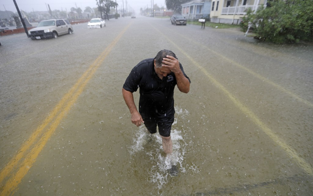 Angel Marshman wades through floodwaters from Tropical Depression Imelda after trying to start his flooded car Wednesday, Sept. 18, 2019, in Galveston...
