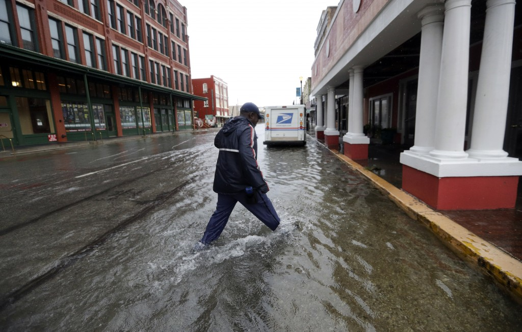 A postman walks through the flooded streets from Tropical Depression Imelda as he deliver mail Wednesday, Sept. 18, 2019, in Galveston, Texas. (AP Pho