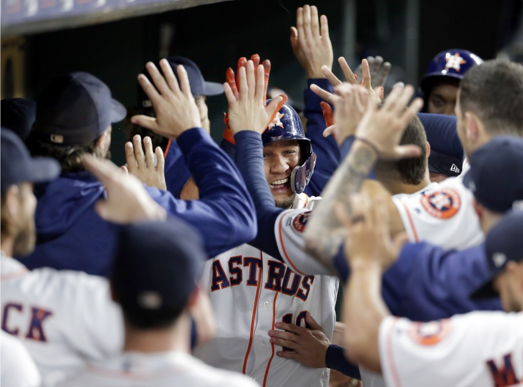 Houston Astros' Yuli Gurriel, center, collects high fives in the dugout after his two-run home run during the fifth inning of a baseball game against ...