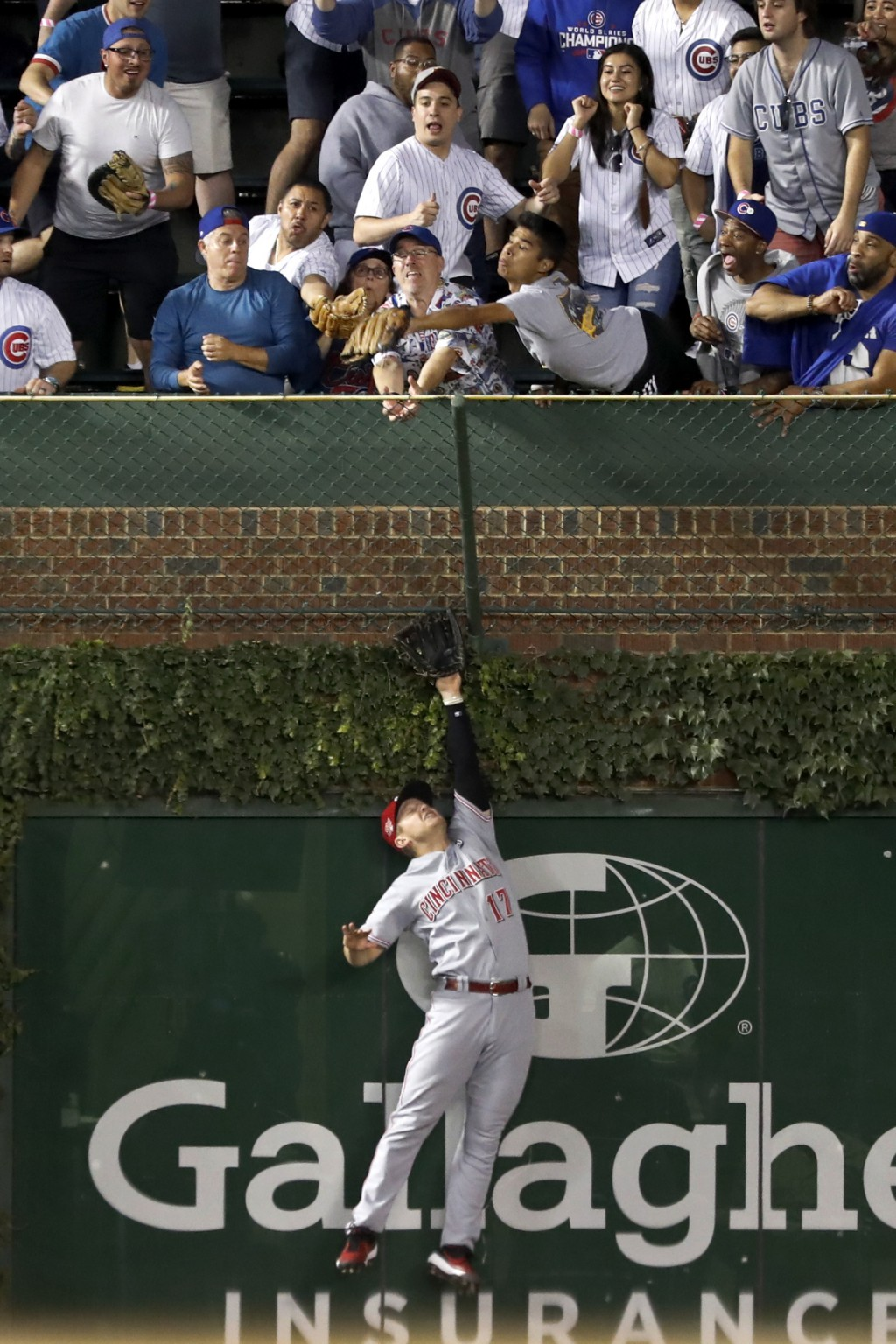 A fan catches a home run by Chicago Cubs' Willson Contreras as Cincinnati Reds' Josh VanMeter leaps for the ball during the seventh inning of a baseba...
