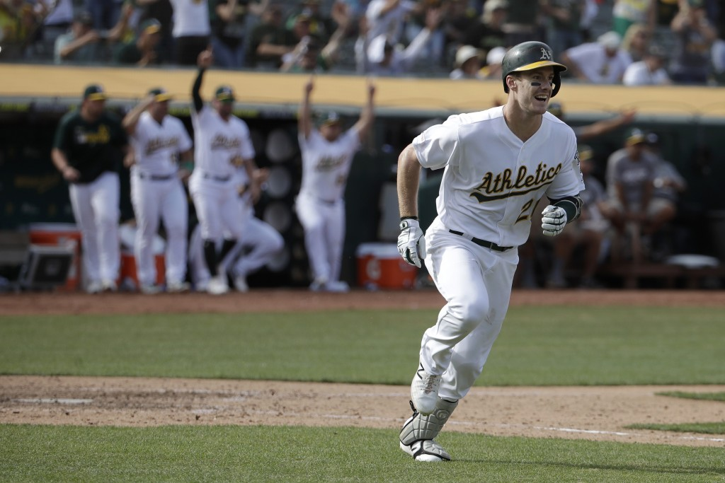 Oakland Athletics' Mark Canha, right, smiles while running up the first base line after hitting a double to score Jurickson Profar for the winning run
