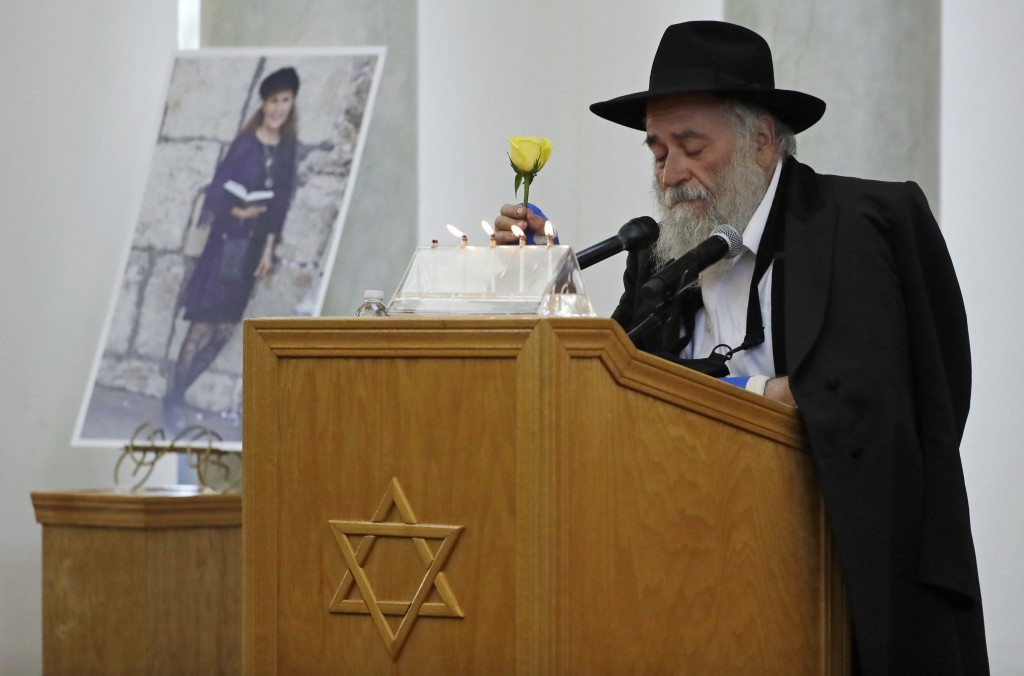 FILE - In this April 29, 2019 file photo, Yisroel Goldstein, Rabbi of Chabad of Poway, holds a yellow rose as he speaks at the funeral for Lori Kaye, ...