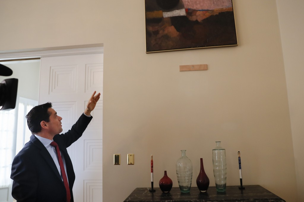 In this Sept. 17, 2019, photo, Carlos Vecchio, an exiled politician who the U.S. recognizes as Venezuela's ambassador,  points to a section of a wall ...