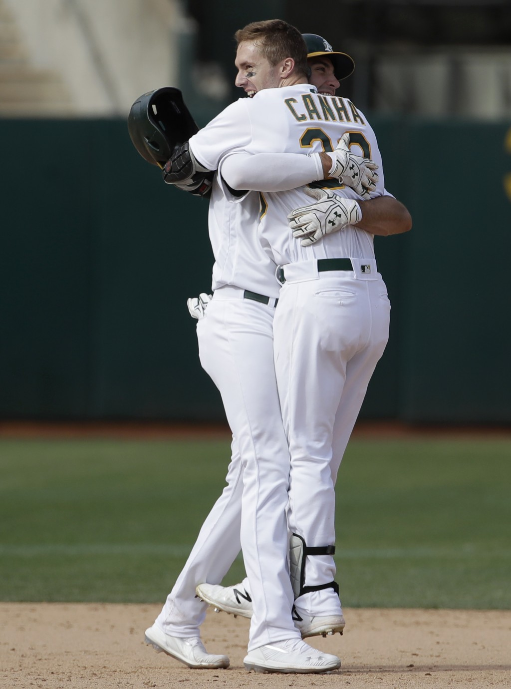 Oakland Athletics' Mark Canha, right, celebrates with Matt Olson after the Athletics defeated the Kansas City Royals 1-0 in 11 innings of a baseball g
