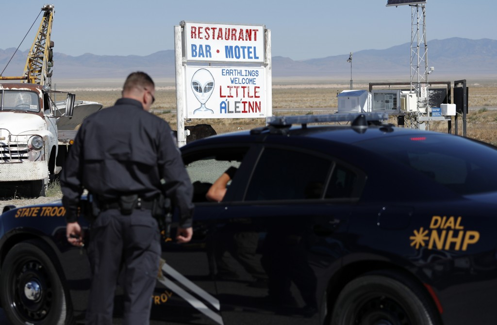 Law enforcement officials stand outside of the Little A'Le'Inn, Wednesday, Sept. 18, 2019, in Rachel, Nev. Visitors descending on the remote Nevada de...