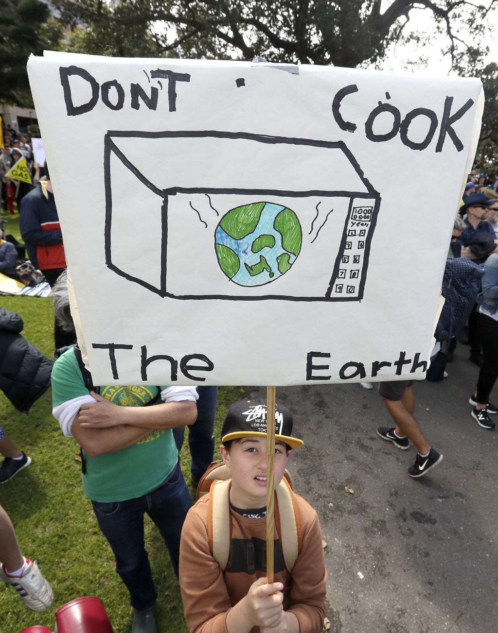 A young activist holds up a handmade placard as thousands of protestors, many of them school students, gather in Sydney, Friday, Sept. 20, 2019, calli