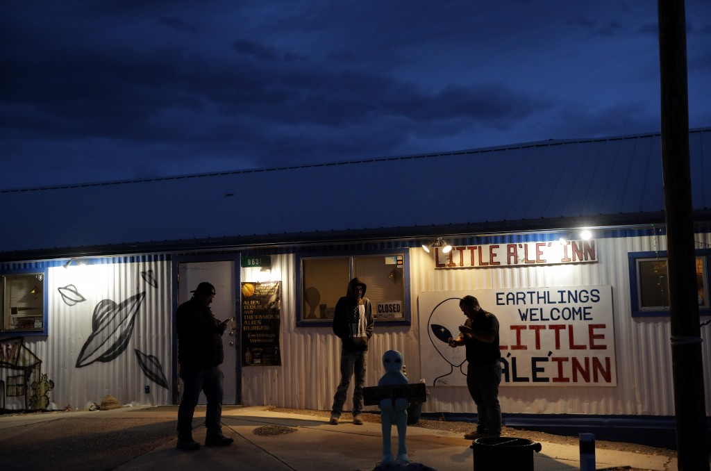 """People stand around the Little A'Le'Inn during an event inspired by the """"Storm Area 51"""" internet hoax, Thursday, Sept. 19, 2019, in Rachel, Nev. Hundr"""