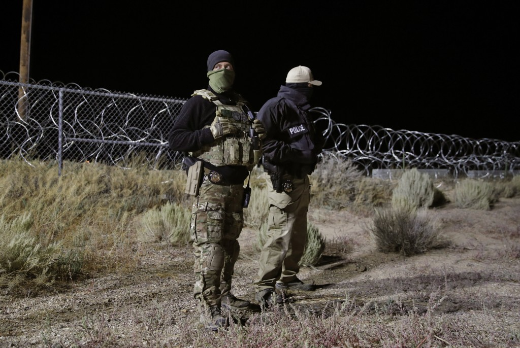 Police officers guard an entrance to the Nevada Test and Training Range near Area 51 Friday, Sept. 20, 2019, near Rachel, Nev. People gathered at the