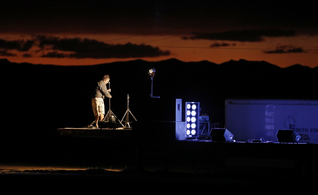 """A man sets up a stage in preparation for an event inspired by the """"Storm Area 51"""" internet hoax near the Little A'Le'Inn motel and cafe, Thursday, Sep"""