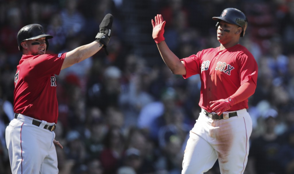 Boston Red Sox's Christian Vazquez, left, and Rafael Devers high-five after scoring on an Xander Bogaerts two RBI single during the second inning of a...