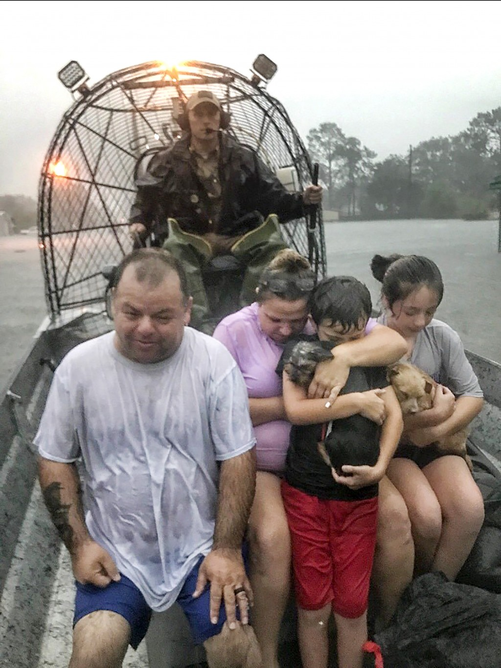 In this photo provided by the Texas Parks & Wildlife Department, a family is rescued via fan boat by a member of the department from the flood waters ...
