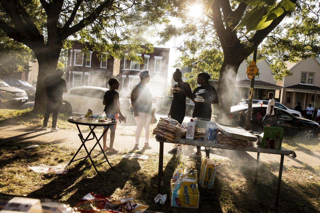 In this Thursday, Aug. 1, 2019, photo, people gather for a barbecue in a vacant lot hosted by Inner-city Muslim Action Network's (IMAN) in Chicago's n