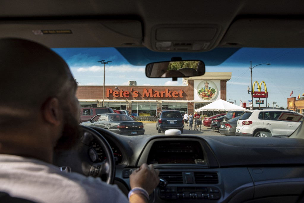 """In this Thursday, Aug.15, 2019, photo, Christopher """"Mad Dog"""" Thomas, drives into Pete's Market in Chicago's Garfield Neighborhood. Thomas organizes a"""