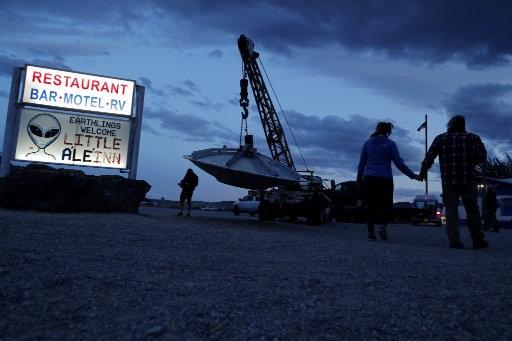 """People walk near the Little A'Le'Inn during an event inspired by the """"Storm Area 51"""" internet hoax, Thursday, Sept. 19, 2019, in Rachel, Nev. Hundreds..."""