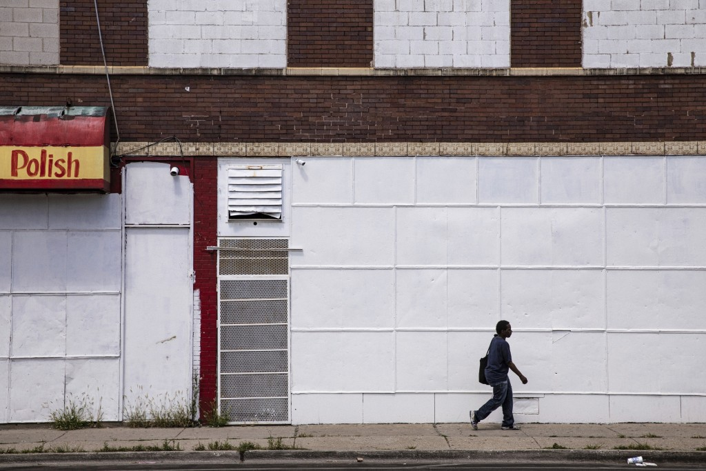 In this Friday, Aug. 9, 2019, photo, a man walks on a sidewalk past boarded up business in Chicago's Englewood neighborhood. As of 2015, roughly 22% o