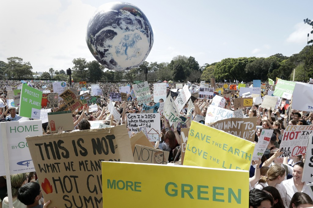 A large inflatable globe is bounced through the crowd as thousands of protestors, many of them school students, gather in Sydney, Friday, Sept. 20, 20