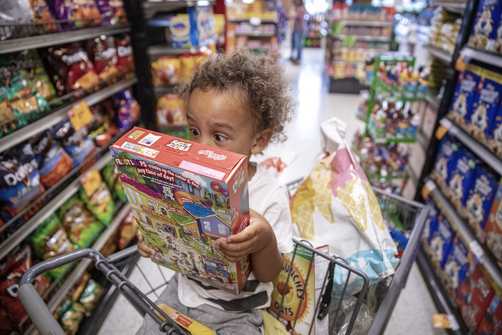 In this Thursday, Aug. 15, 2019, photo, Rian Gatewood-Hillestad reacts to cartoons printed on a cereal box while shopping with his parents at Pete's M...